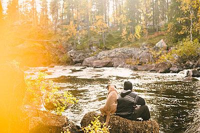 Woman sitting at river - p312m2091610 by Matilda Holmqvist