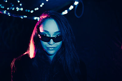 Portrait of confident young woman wearing sunglasses in illuminated restaurant - p426m2205291 by Maskot