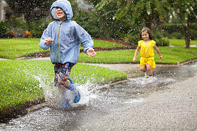 Boy and sister wearing rubber boots running and splashing in rain puddle - p924m958048f by Kinzie Riehm