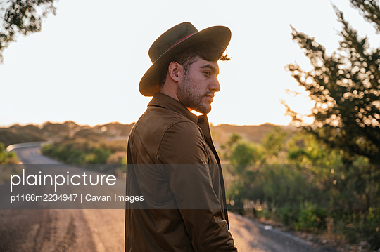 Handsome explorer man standing on road and enjoying of sunrise - p1166m2234947 by Cavan Images