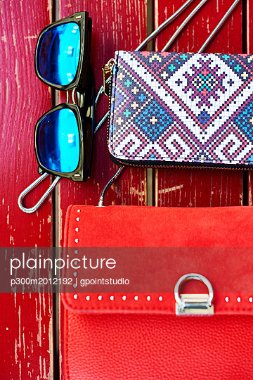 Sunglasses, purse and handbag on red wooden bench - p300m2012192 von gpointstudio