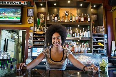 Portrait confident female bartender behind counter - p1192m1184125 by Hero Images