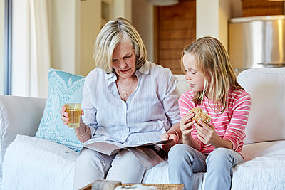 Grandmother and granddaughter sitting side by side on the couch looking at a book - p300m1449923 by Martina Ferrari