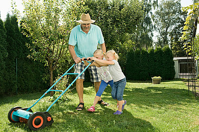 Germany, Bavaria, Grandfather with children mowing lawn - p300m752560f by Robert Niedring
