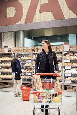 Woman pushing shopping cart against female standing by bread rack at supermarket - p426m1451884 by Maskot