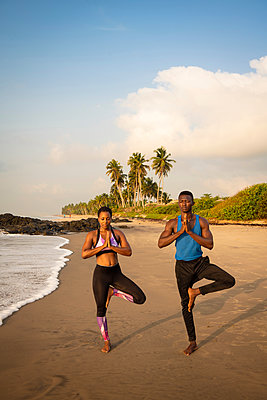 Couple practising yoga on beach - p429m2091772 by Ben Pipe Photography