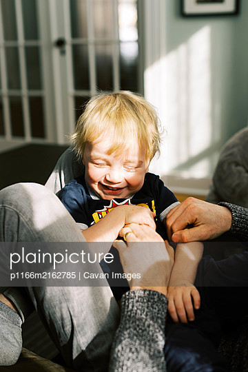 A two year old boy laughing with his eyes closed while being tickled. - p1166m2162785 by Cavan Images