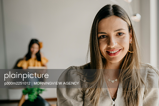 Beautiful woman in waiting area while daughter sitting in background - p300m2251012 by MORNINGVIEW AGENCY