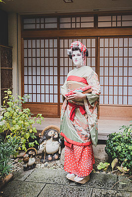 A woman dressed in the traditional geisha style wearing a kimono  - p1345m2055589 by Alexandra Kern