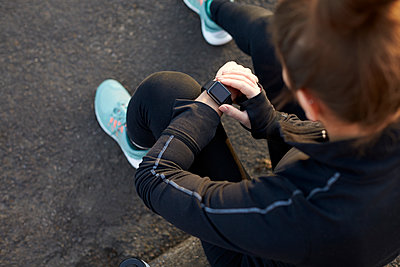 Young Woman Checks Activity Tracker During Outdoor Exercise - p1407m1508975 by Monkey_Images