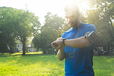 Runner in urban park checking his smartwatch - p300m1549950 by Steve Brookland