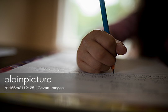 Cropped image of girl writing homework on table at home - p1166m2112125 by Cavan Images