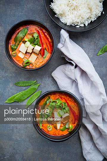 Two bowls of red Thai Curry with snow peas, carrots, bell pepper, spring onions and smoked tofu - p300m2059418 by Larissa Veronesi