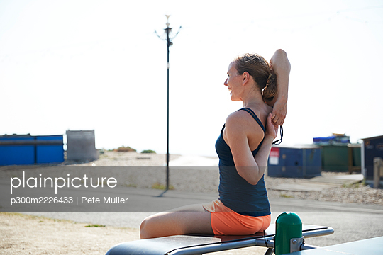 Sportswoman stretching hands behind back while sitting on bench - p300m2226433 by Pete Muller