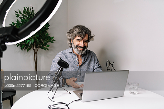 Senior male freelancer podcasting with laptop on table at home office - p300m2277158 by COROIMAGE