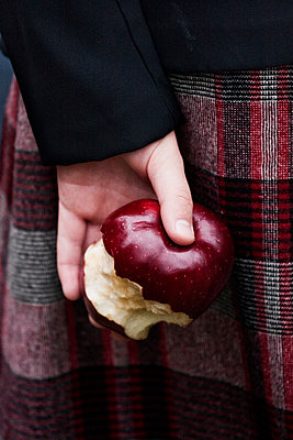 Girl Holding Eaten Apple Behind Back - p1331m1169231 by Margie Hurwich