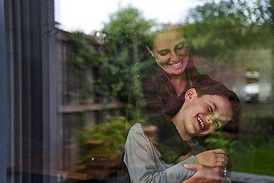 Woman embracing cheerful son at home seen through window - p300m2197374 by Stefanie Aumiller