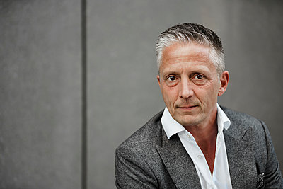Serious male entrepreneur against gray wall - p300m2276439 by Sandro Jödicke