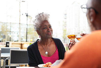 Smiling woman toasting drink with man at restaurant - p300m2294119 by Pete Muller