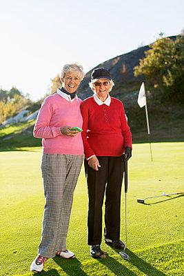 Full length portrait of senior female golfers standing on golf course - p426m920107f by Kentaroo Tryman