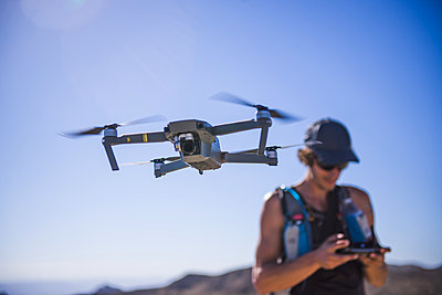 Man operating drone (unmanned aerial vehicle) against blue sky, Nelson, Nevada, USA - p924m2090606 by Alex Eggermont