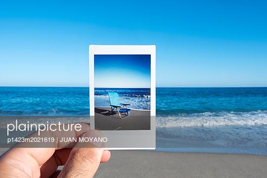 Mann hält ein Foto am Strand - p1423m2021619 von JUAN MOYANO