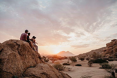 Namibia, Spitzkoppe, friends sitting on a rock watching the sunset - p300m2080835 by letizia haessig photography