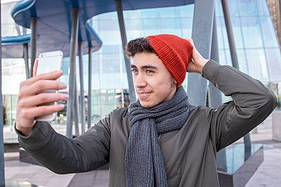 Young man wearing knit hat taking selfie through mobile phone in city - p300m2242919 by Ignacio Ferrándiz Roig