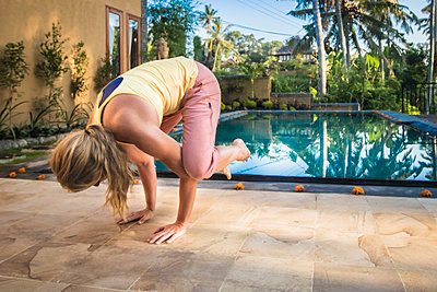 Woman doing exercises near pool - p343m1475790 by Suzanne Stroeer