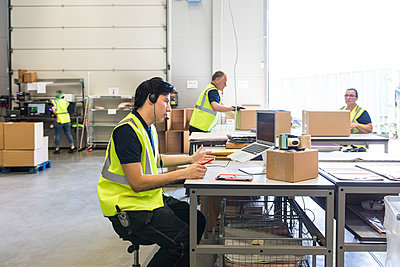 Young customer service representative talking through headset while coworkers at warehouse - p426m2018802 by Maskot