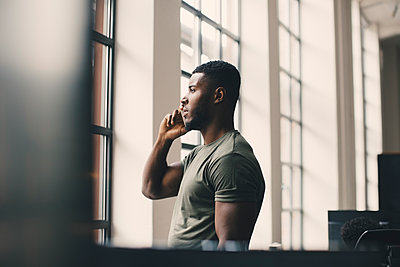 Male entrepreneur talking on mobile phone while looking through window in office - p426m2270437 by Maskot