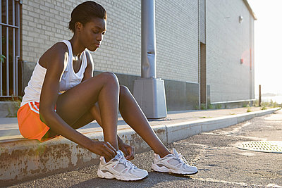 Runner sitting on sidewalk - p9245283f by Image Source