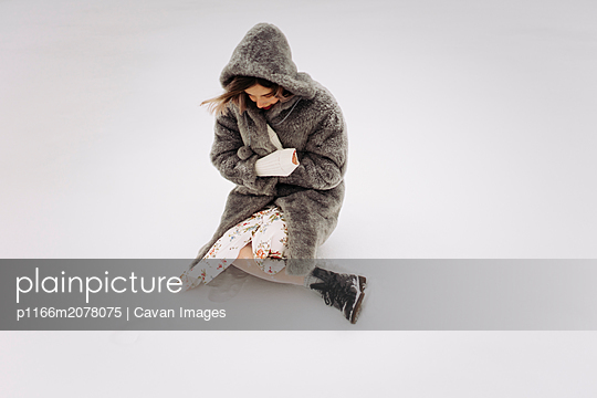 Frozen girl sitting in the snow - p1166m2078075 by Cavan Images