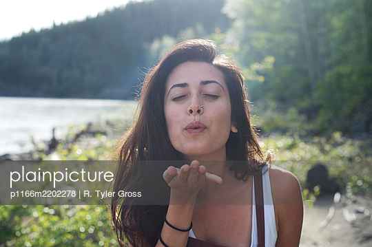 Portrait of woman blowing hand, Yukon, Canada - p1166m2202278 by R. Tyler Gross