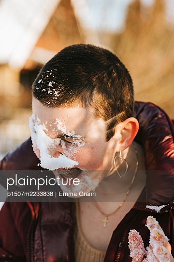 Teenager playing in snow - p1507m2233838 by Emma Grann