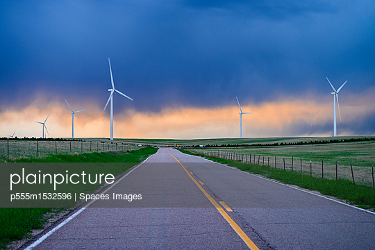 plainpicture | Photo library for authentic images - plainpicture p555m1532596 - Wind turbines near road at ... - plainpicture/Blend Images/Spaces Images