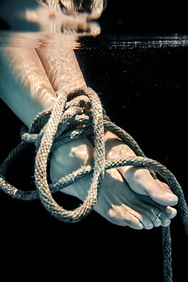 Woman's Feet Tied Up with Rope Drowning Under Water  - p1019m2107496 by Stephen Carroll