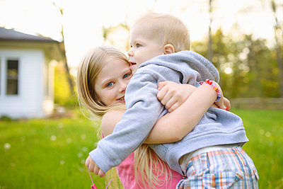 Portrait of happy girl carrying brother while standing in backyard - p1166m1182874 by Cavan Images