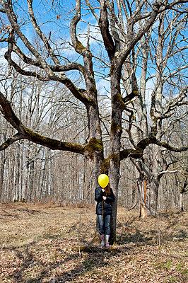 Girl hiding face behind a yellow balloon - p1412m1548050 by Svetlana Shemeleva