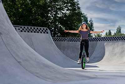 Young woman riding unicycle in skatepark - p300m2132495 by Stefan Schurr