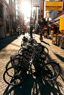 Japan, Osaka Prefecture, Osaka, Sun setting over bicycles parked on Dotonbori street - p300m2202588 by klublu
