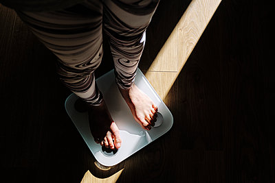 Young woman standing on weight scale in dark at home - p300m2264632 by Antonio Ovejero Diaz