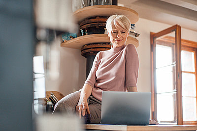 Female freelance worker with laptop sitting on kitchen counter at home - p300m2266987 by Robijn Page