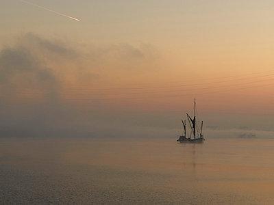 Sailing boat in dawn mist, Thames Estuary, Dartford, London. - p8552495 by Richard Bryant