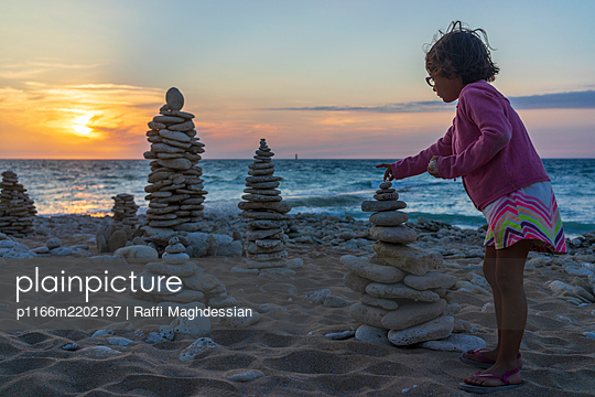 Girl stacking pebbles on beach - p1166m2202197 by Raffi Maghdessian