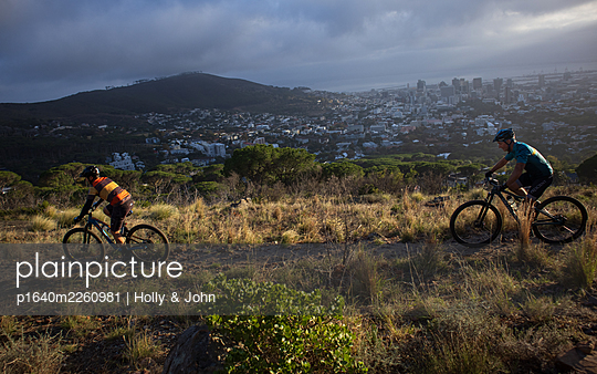 Two mountain bikers on the move, cityscape in the background - p1640m2260981 by Holly & John