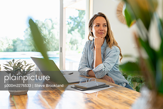Blond hair entrepreneur sitting with laptop at table while looking away - p300m2276533 by Steve Brookland