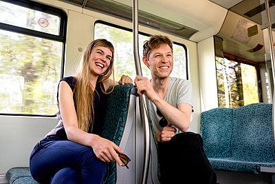 Junges Paar in der Bahn - Lachen - p1212m1138827 von harry + lidy