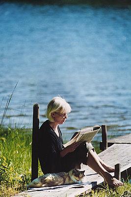 Cat hanging out with mature woman reading newspaper on wooden bridge - p1418m1559101 by Jan Håkan Dahlström