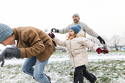 Father and two children having a snowball fight - p300m2080993 by Katharina Mikhrin